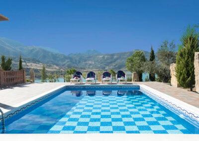 The swimming pool at El Dolmen de Alaju, El Gastor overlooks the surreal blue waters of Embalse de Zahara Lake