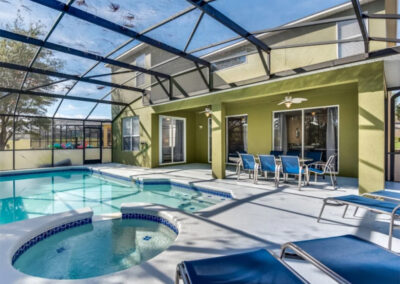 The covered lanai, alfresco dining area, swimming pool & spillover tub at Emerald Island Resort 13, Kissimmee
