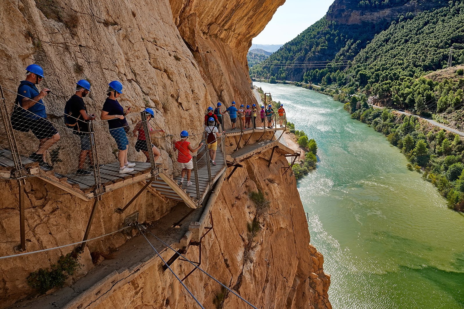 """If you are feeling brave, then one of the most spectacular gorge views is from the Caminito del Rey, The King's Little Path. Pinned to the steep walls of the El Chorro Gorge, the 1 metre wide wooden walkway hangs 100 meters above the river below. It has been known in the past as the """"world's most dangerous walkway"""" following five deaths in 1999 and 2000. After closing for four years, the Caminito reopened in 2014 after repairs and new safety features were added."""