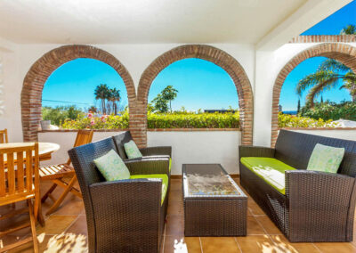 The covered terrace with outdoor dining & sitting area at Villa Rucula, Estepona
